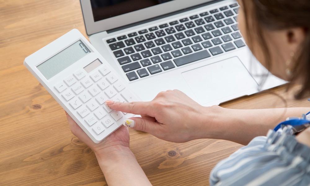 ブログ、ライターの副業の税金を計算する女性